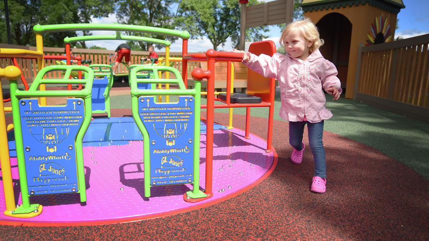 Briana Sanchez / Tribune  Anneliese Nelson, 2, runs around the wheelchair accessible merry-go-round at Destination Playground Friday, June 23, in Willmar. Nelson and her family came from Colorado to visit her grandma who lives in Morris.