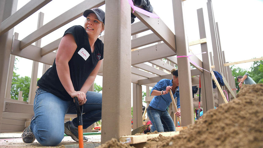 Briana Sanchez / Tribune  Terwisscha Construction employees Kayla Swanson and Natalie Tagtow volunteer with at the playground build Friday, May 19, at Destination Playground at Robbins Island in Willmar. Swanson and Tagtow had to redig the wholes because of the rain.